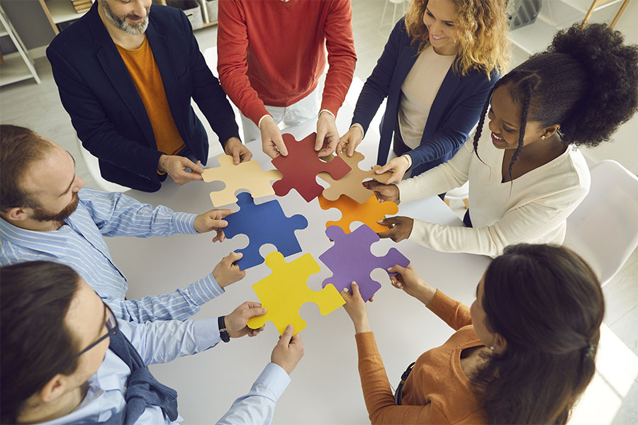 About Our Agency - Portrait of a Diverse Group of Employees Standing in a Conference Room While Holding Colorful Puzzle Pieces