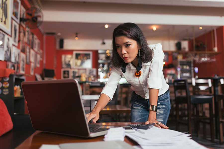 Business Insurance - Portrait of a Young Female Business Owner Standing in Her Restaurant While Working on Paperwork on Her Laptop
