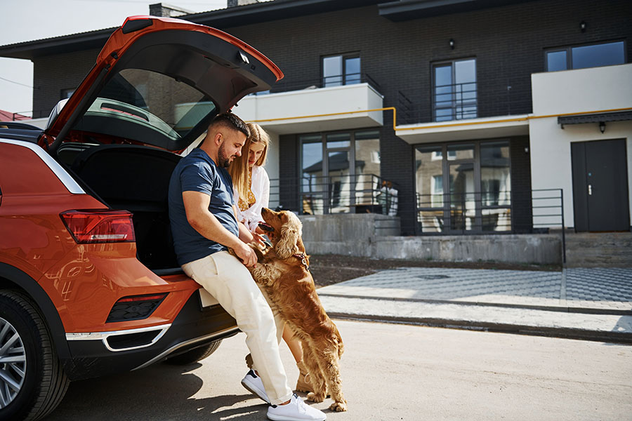 Contact - Portrait of a Young Couple Sitting in the Back Trunk of Their SUV While Playing with Their Dog in Front of Their House