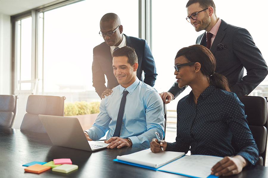 Employee Benefits - Cheerful Group of Employees Having a Business Meeting in a Modern Conference Room While Using a Laptop