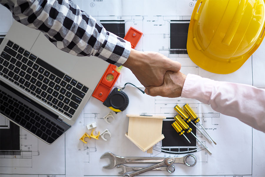 Specialized Business Insurance - Closeup Portrait of Two Contractors Shaking Hands Over a Table with Blueprints and Construction Tools